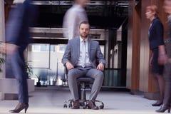 El hombre de negocios que se sienta en silla de la oficina, gente agrupa el paso cerca Foto de archivo libre de regalías