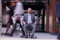 El hombre de negocios que se sienta en silla de la oficina, gente agrupa el paso cerca Imagen de archivo