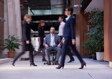 El hombre de negocios que se sienta en silla de la oficina, gente agrupa el paso cerca Foto de archivo