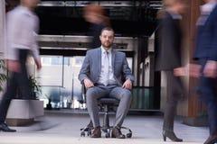 El hombre de negocios que se sienta en silla de la oficina, gente agrupa el paso cerca Fotos de archivo libres de regalías