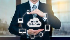 El hombre de negocios que sostenía una nube conectó con muchos objetos en concepto de la pantalla virtual sobre Internet de cosas Imagen de archivo