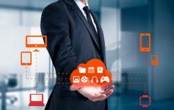 El hombre de negocios que sostenía una nube conectó con muchos objetos en un concepto de la pantalla virtual sobre Internet de co Imagen de archivo