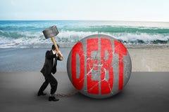 El hombre de negocios que sostiene el martillo que golpea la bola agrietada de la DEUDA con el mar sea Imágenes de archivo libres de regalías