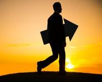 El hombre de negocios que sostiene la flecha y guarda el caminar imágenes de archivo libres de regalías