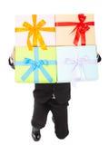 El hombre de negocios que sostiene los regalos y se arrodilla abajo imagenes de archivo