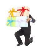 El hombre de negocios que sostiene los regalos y se arrodilla abajo Aislado en blanco imagenes de archivo