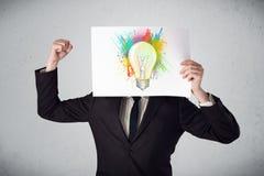 El hombre de negocios que sostiene una cartulina con la pintura salpica y lightbul Imagen de archivo libre de regalías