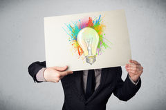 El hombre de negocios que sostiene una cartulina con la pintura salpica y lightbul Foto de archivo