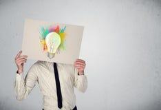 El hombre de negocios que sostiene una cartulina con la pintura salpica y lightbul Imágenes de archivo libres de regalías