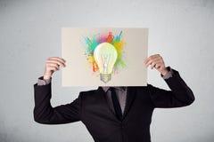 El hombre de negocios que sostiene una cartulina con la pintura salpica y lightbul Fotografía de archivo libre de regalías