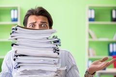 El hombre de negocios que tiene problemas con papeleo y carga de trabajo imagen de archivo