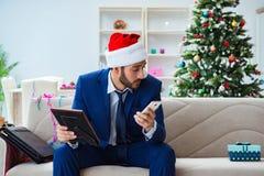 El hombre de negocios que trabaja en casa durante la Navidad Imagen de archivo libre de regalías