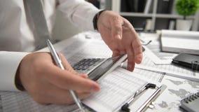El hombre de negocios que trabaja en la oficina y que calcula finanzas, lee y escribe informes concepto de la contabilidad financ metrajes