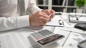 El hombre de negocios que trabaja en la oficina y que calcula finanzas, lee y escribe informes concepto de la contabilidad financ almacen de metraje de vídeo