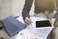 El hombre de negocios que usa el ordenador portátil y el smartphone y la tableta por el año financiero analítico 2017 del gráfico Foto de archivo