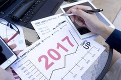 El hombre de negocios que usa el ordenador portátil y el smartphone y la tableta por el año financiero analítico 2017 del gráfico Imagen de archivo libre de regalías