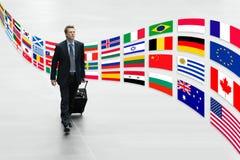 El hombre de negocios que viaja con las banderas internacionales de la carretilla dispara concepto Fotos de archivo