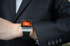 El hombre de negocios recibe la notificación del mensaje en el reloj elegante Foto de archivo