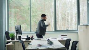 El hombre de negocios rico feliz del individuo está bailando con efectivo en la oficina entonces que lanza el dinero en aire, los metrajes