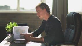 El hombre de negocios rubio joven sentarse en la oficina moderna, explica el trabajo a los miembros Carta de negocio financiera c almacen de video