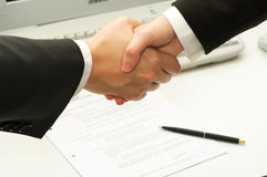 El hombre de negocios sacude las manos después de firmar un contrato Imagen de archivo libre de regalías