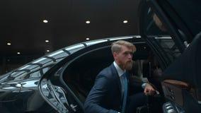 El hombre de negocios sale de un coche ejecutivo, encargado superior viene a la reunión importante, hombre rico famoso sale de su metrajes