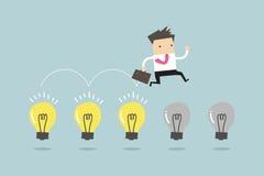 El hombre de negocios salta en bombillas Imágenes de archivo libres de regalías