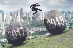 El hombre de negocios salta entre los números 2017 y 2018 Imágenes de archivo libres de regalías