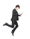 El hombre de negocios salta la PC de la tableta conmovedora Fotografía de archivo