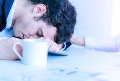 El hombre de negocios se cae dormido en la tabla de la oficina fotografía de archivo
