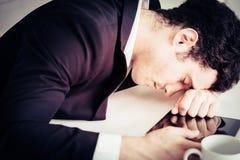 El hombre de negocios se cae dormido en la tabla de la oficina foto de archivo libre de regalías