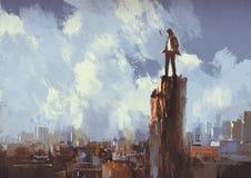 El hombre de negocios se coloca en el pico que mira la ciudad Foto de archivo libre de regalías