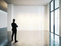 El hombre de negocios se coloca en interior blanco en blanco del museo con el piso concreto horizontal fotos de archivo