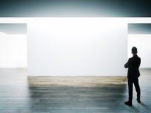El hombre de negocios se coloca enfrente de la pared blanca grande en interior del museo con el piso de madera horizontal fotos de archivo