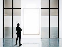 El hombre de negocios se coloca enfrente de marcos en blanco en galería contemporánea foto de archivo libre de regalías