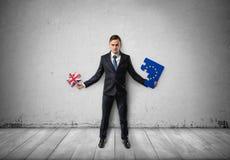 El hombre de negocios se coloca que lleva a cabo pedazos de rompecabezas con la UE y las banderas BRITÁNICAS en ellas Imagenes de archivo