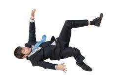 El hombre de negocios se está cayendo abajo Aislado en el fondo blanco foto de archivo
