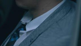 El hombre de negocios se est? sentando en un coche mirada en el reloj metrajes
