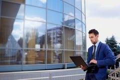 El hombre de negocios se sentó afuera con el ordenador portátil, cuaderno Imágenes de archivo libres de regalías