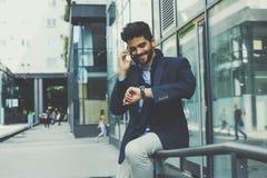 El hombre de negocios se sienta delante del edificio que habla en móvil y c fotos de archivo