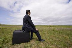 El hombre de negocios se sienta en su bagaje Imágenes de archivo libres de regalías