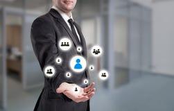 El hombre de negocios señala a la icono-hora, al reclutamiento y al concepto elegido Imágenes de archivo libres de regalías
