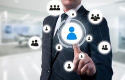 El hombre de negocios señala a la icono-hora, al reclutamiento y al concepto elegido Foto de archivo libre de regalías