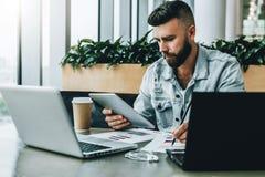 El hombre de negocios serio joven se está sentando en oficina delante de los ordenadores portátiles, usando la tableta digital, h fotografía de archivo