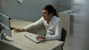 El hombre de negocios serio trabaja en la mesa Comerciante que mira la acci?n de la pantalla en l?nea metrajes