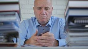 El hombre de negocios serio y confiado Read Mobile Phone manda un SMS a la oficina interior imagen de archivo libre de regalías