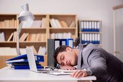 El hombre de negocios soñoliento que trabaja en oficina imagenes de archivo