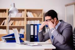 El hombre de negocios soñoliento que trabaja en oficina foto de archivo