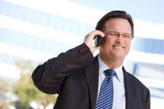 El hombre de negocios sonríe mientras que él habla en su teléfono celular Fotografía de archivo