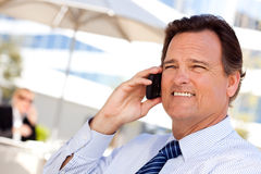 El hombre de negocios sonríe mientras que él habla en su teléfono celular Imágenes de archivo libres de regalías